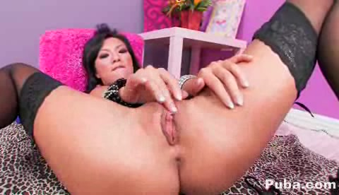 Asian Chick Posing Her Alluring Body As She Lays Prone On A Pink And Brown Comforter Wearing Black Stockings With Suspenders And High Heels Before She Gets Her Dildo And Shoves It Deep In Her Pussy In A Violet And Pink Room.