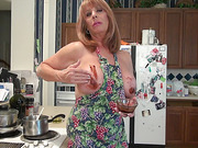 Sexy old lady in an apron on her naked body cooking something and soiling her tits and pussy with chocolate sauce
