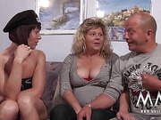 Curly blonde mature and her husband both in corsets hanging out with brunette chick in a cap