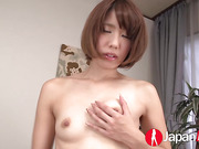 Cute Japanese chick with skinny body in multi-colored bikini teases as she unties her bra and show her small tits then she takes off her panty and rubs her pussy on a green couch before she rubs it with a pink vibrator in different positions then she suck