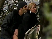 Blonde in black balances while her pussy is devoured by her guy's rod during outdoor fuck.