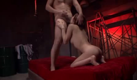 Lusty Japanese Chick With Indulging Boobs And Luscious Body Kneels Down Naked On A Red Bed And Sucks A Hunk Stud's Balls Before She Bounces On His Cock.