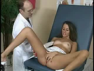 Stunning Patient Lays Back On A Blue Seat And Expose Her Juicy Tits Wearing Her White And Gray Scrub Suit And White High Heels While She Dips Her Fingers In Her Wide Open Pussy In Front Of Her Doctor.